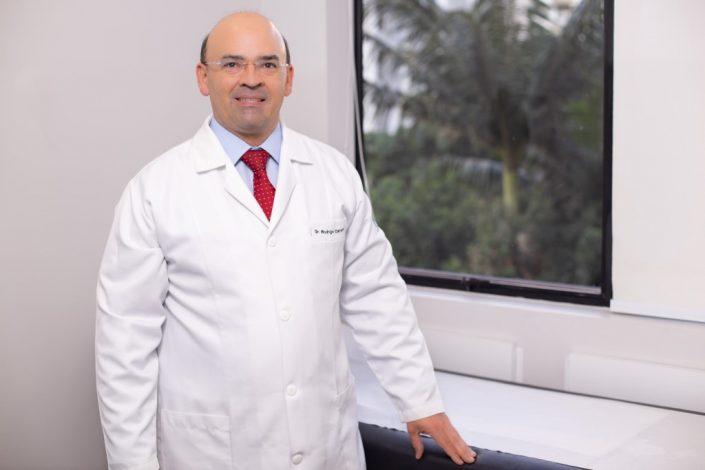 Retrato do doutor Rodrigo Campos, apoiando sua mão na maca dentro do consultório da Clínica Zequi