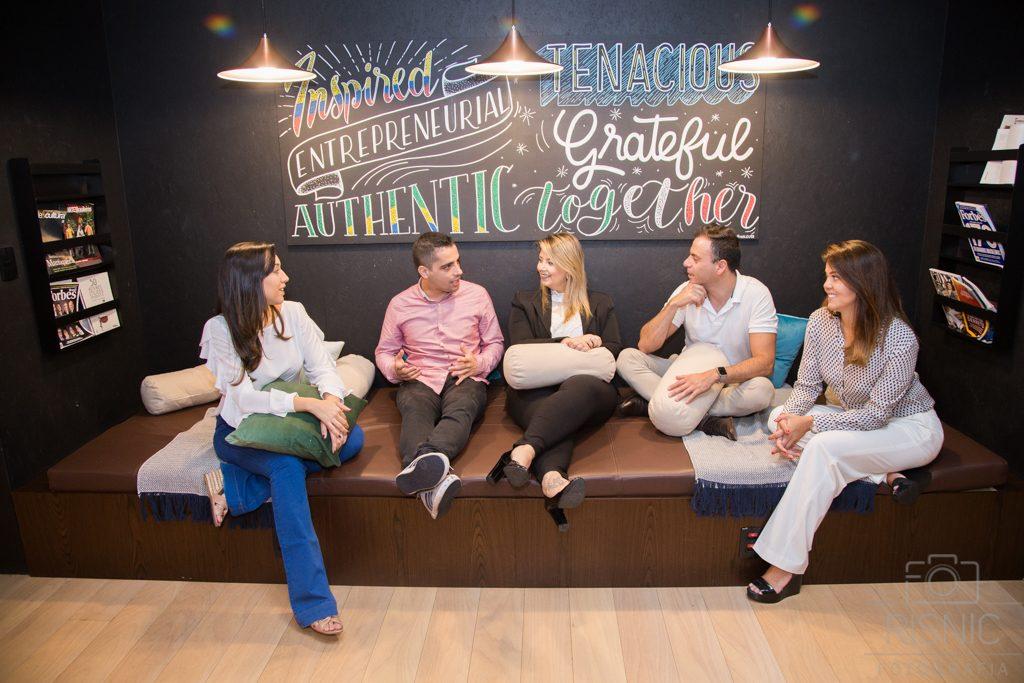 Produção de Retratos Corporativos, temos a equipe da Somos Nuvem descontraída no sofa, no escritório da Wework Itaim