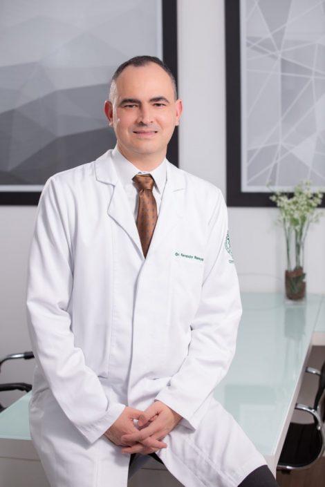 Retrato do Doutor Felipe Ramos, em pé encostado na mesa do consultório