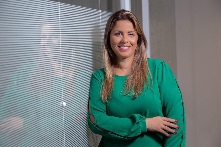 Retrato Corporativo da Renata Munhoz. Na foto aparece de pé ao lado da parede de vidro do escritório