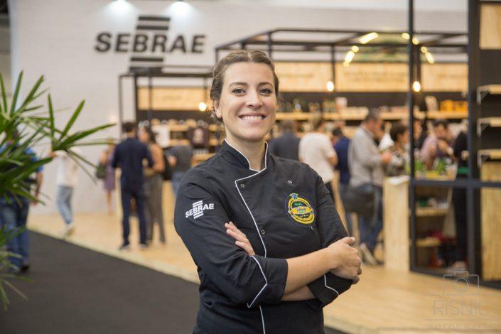 Na foto está a Chef Mariana Pelozio em frente ao Stand do Sebrae na Feira Sirha. Fotografia Profissional de Retrato Corporativo