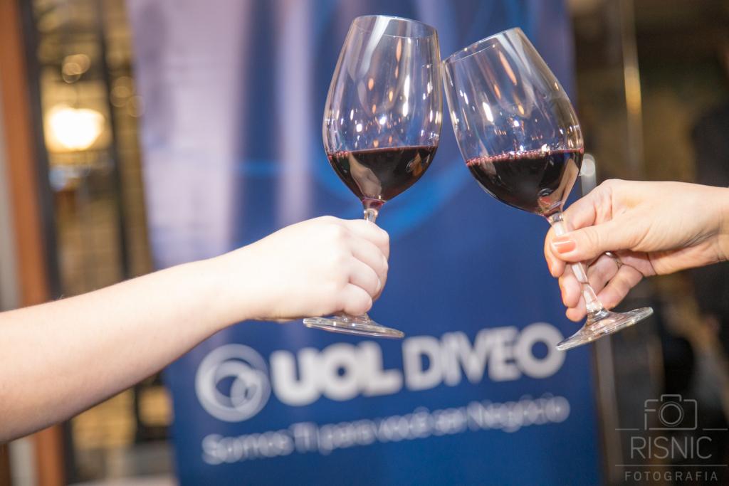 Nesta foto temos um brinde com taças de vinho em frente ao banner da Uol Diveo, em evento promovido no Le Bife