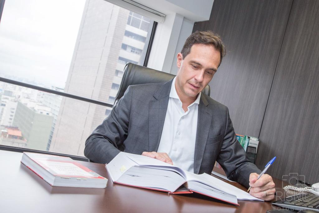 Retrato Corporativo do sócio Mauricio Loddi, do escritório Loddi Ramires Advogados. Ele está sentado em sua mesa, em sua sala.