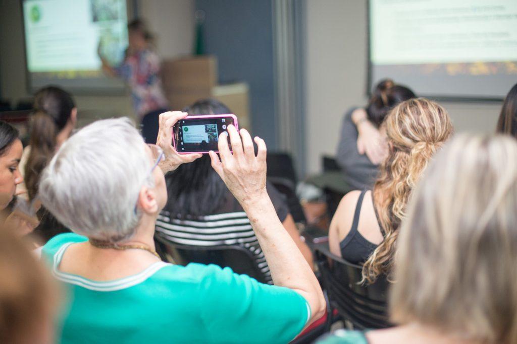 Foto com senhora fotografando através do celular uma palestra no Simpósio realizado no Hospital São Camilo, fotografia corporativa em eventos