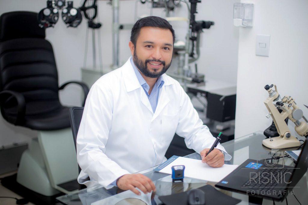 Retrato corporativo do médico oftalmologista Diego Ruiz, sentado em seu consultório