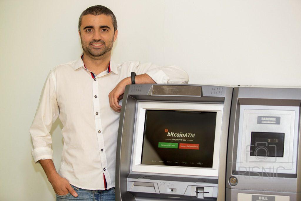 Retrato Corporativo de Arthur Souza, ao lado de caixa automático de criptomoedas