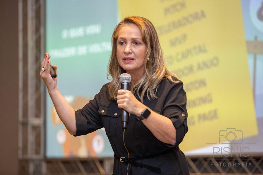 Mulher apresentando a palestra durante evento corporativo