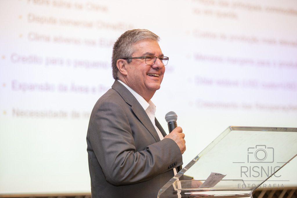 Foto que mostra homem sorridente durante evento corporativo