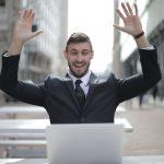 Retrato de homem em frente ao computador com mãos ao alto